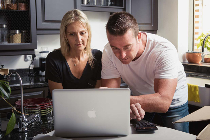 Husband and wife on laptop looking worried